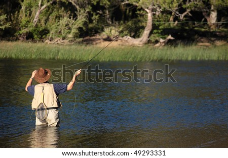 A fisherman casts his fly rod hoping for a bite. - stock photo
