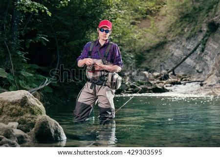 A fisherman chooses bait for trout fishing in the river. Fishing in the creek fly fishing lure. Activity sports fishing wading.