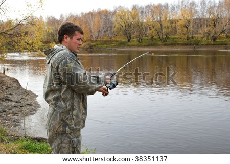 a fisherman fishes on the river in autumn