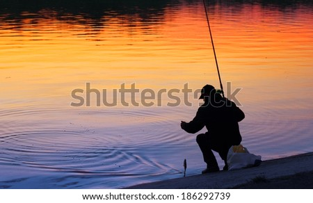 A fisherman fishing at sunset just caught a fish - stock photo