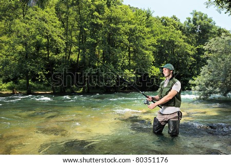 A fisherman fishing on a river with forest in the background - stock photo