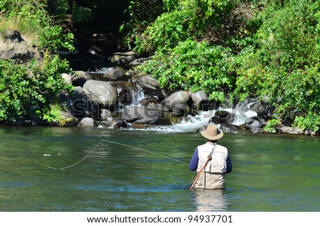 A fisherman fly fishes for Trout fish in Tongariro river near Taupo lake, New Zealand. - stock photo