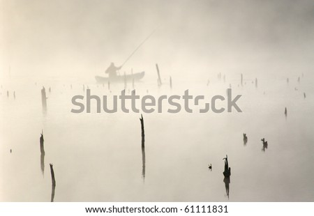 A fisherman in a boa.t Early morning.  Old dried trees stick out from water. - stock photo