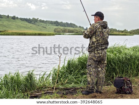 A fisherman is fishing from the shore