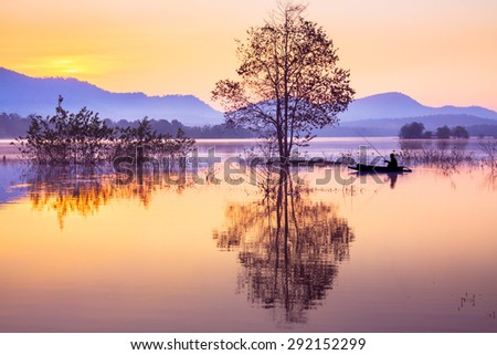 a fisherman is fishing on boat in lake - stock photo