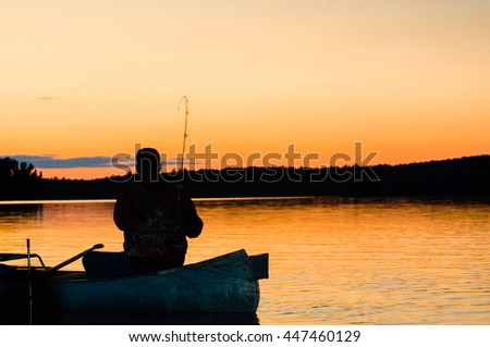 A fisherman is silhouetted against an orange sunset on the lake in the Boundary Waters Canoe Area in the North Woods of northern Minnesota. This is the American side of Quetico National Park in Canada