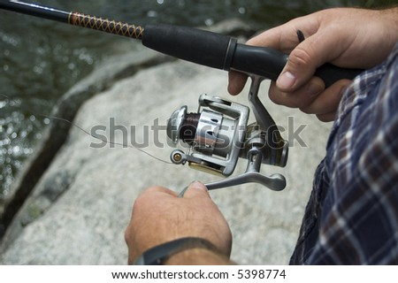 A fisherman lets his lure sink a little before reeling it in, in an attempt to catch a fish with his spin reel.