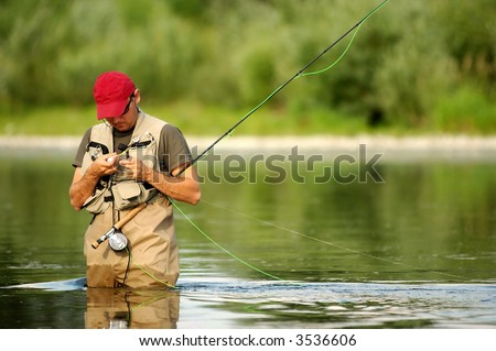 A fisherman make ready angling on the river - stock photo