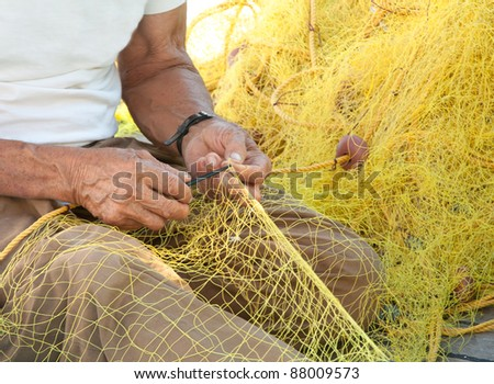 A fisherman mending his yellow fishing net on his boat in Greece. - stock photo