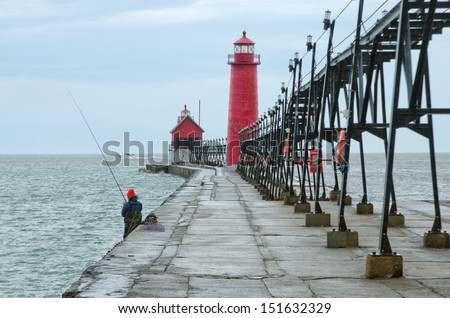 A fisherman on the pier of The Grand Haven South Lighthouse on the eastern shore of Lake Michigan. in late winter.  - stock photo