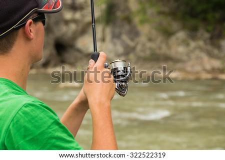 A fisherman on the river bank. Fishing as an active lifestyle. Fishing on the mountain river. Fisherman standing on a rock fishing. - stock photo
