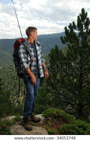 A fisherman on top of a mountain looking at the view