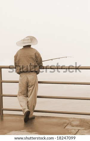 A fisherman relaxes during a cold, foggy morning. - stock photo