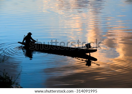 A fisherman's boat floating on the calm water under amazing sunset - stock photo