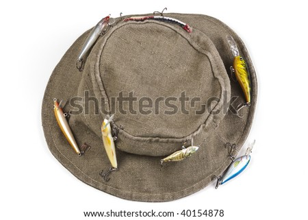 A fisherman's hat with lures attached shot against white background with soft shadow