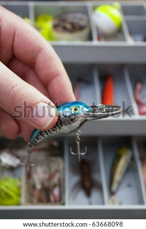 A fisherman selects just the right lure from his tackle box that he is going to fish with. - stock photo