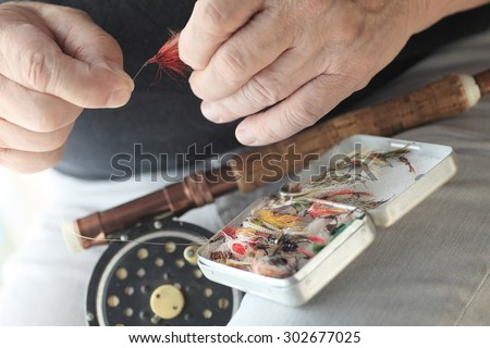 A fisherman with fly fishing pole and box of artificial lures holds a red fly. - stock photo