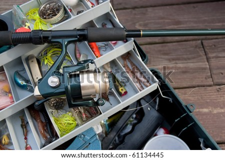 A fishermans rod reel and tackle box filled with lures and bait ready for the start of fishing season. - stock photo