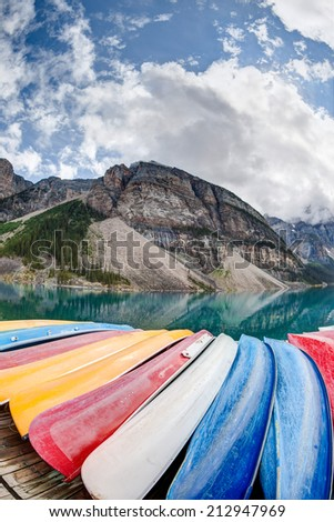 A fisheye view of Moraine Lake in the Canadian Rockies, with vibrant colored canoes on the foreground and the Valley of the Ten Peaks in the background. Vertical Orientation. - stock photo