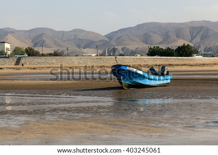 A fishing boat getting stuck in one of Muscat beaches in low tide with few tourists wandering around. - stock photo