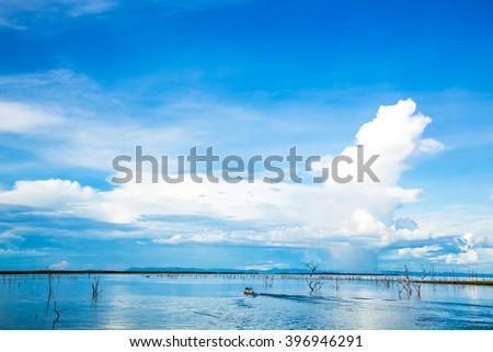 A fishing boat going out.  Lake Kariba.  Clear water and blue sky.  Clouds up above.  Zambezi Valley.  Zimbabwe, Africa. - stock photo