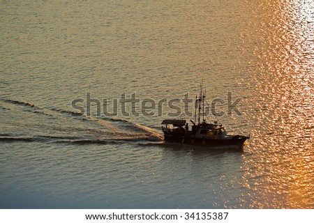 A fishing boat moving through quiet sea with orange sunset light