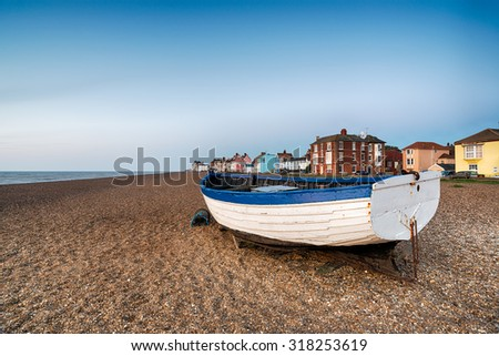 A fishing boat on the shingle beach at Aldeburgh on the Suffolk coast - stock photo