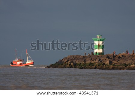 A fishing boat returns to the harbor of Scheveningen, Netherlands - stock photo