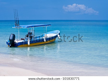 A fishing boat sits at the beach waiting - stock photo