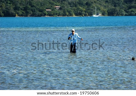 A fishing guide in Honduras casts a fly at a bone fish - stock photo