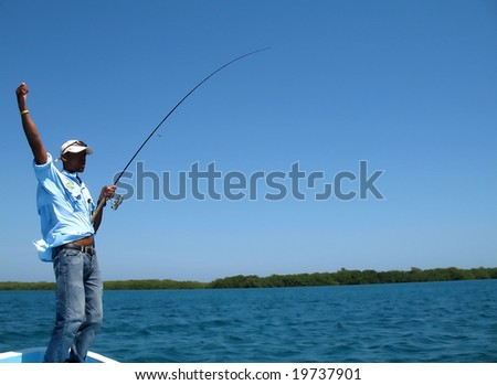 A fishing guide in honduras has hooked into a large fish, fishing from small boat, and shows his pleasure - stock photo