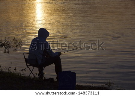 A fishing man at the river bank at sunset in summer