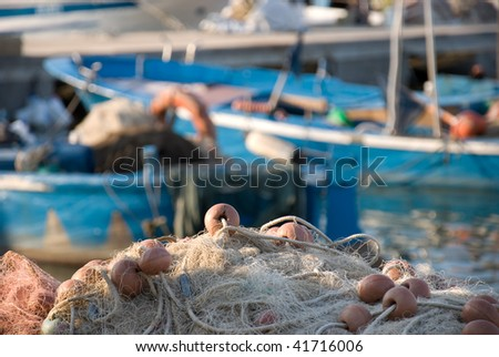 A fishing net in front - boats in the background. - stock photo
