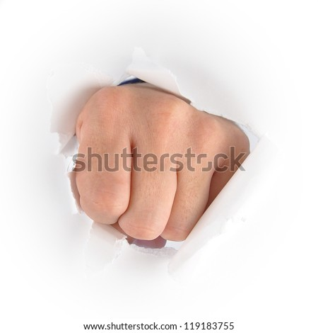 A fist hand is punching through a white piece of paper. Use it for an anger or impact concept. - stock photo