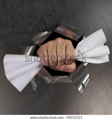 A fist punching through a sheet metal and creating a hole burst - stock photo