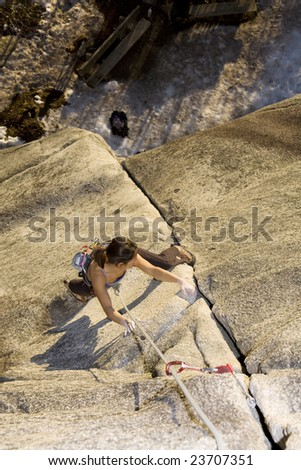 A fit and attractive girl climbs a granite rock in Squamish British Columbia Canada. - stock photo