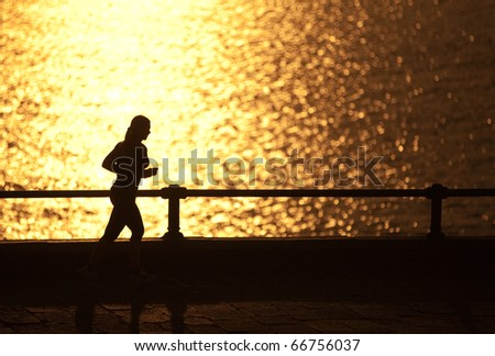 A fit and attractive woman running on the street with the sea amd the sun behind her - stock photo
