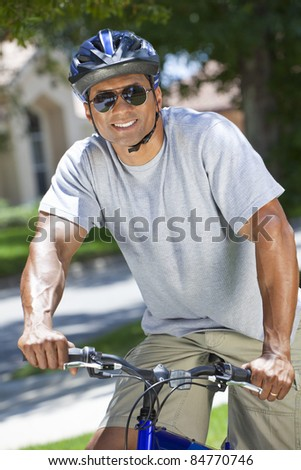 A fit and healthy African American man riding bicycle in the summer.