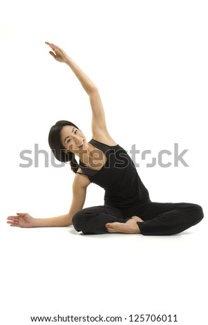 A fit Asian woman sits and stretches - stock photo