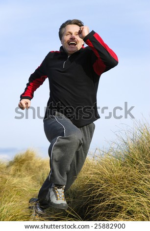 A fit fit forties man is laughing as he runs at speed through san dunes, - stock photo