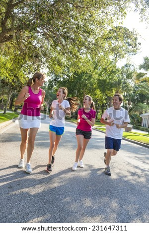 A fit happy and healthy family, man, woman, mother, father parents and two girl children road running and having fun outside together in summer sunshine - stock photo
