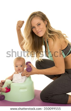 A fit mom trying to help her baby girl be fit, by lifting weights. - stock photo