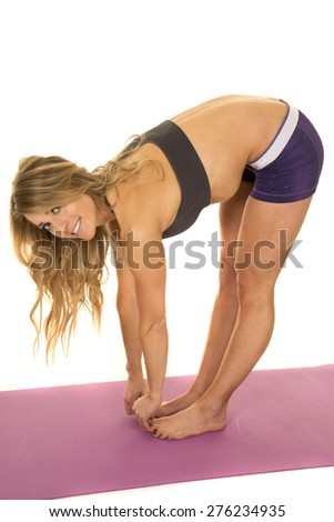 A fit woman bending over and stretching out her body. - stock photo
