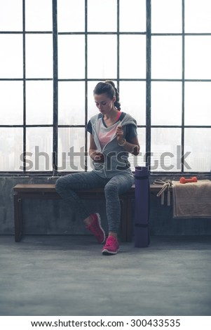 A fit woman casually takes her sweatshirt off, as she is sitting on a city loft gym bench, getting ready to do a workout. - stock photo