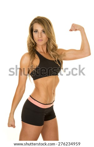 A fit woman with a serious expression on her face, flexing her arms. - stock photo