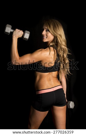 a fit woman with a smile on her face, looking over her shoulder with weights. - stock photo