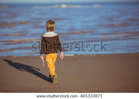 A five-year-old boy is coming to the sea with a short stick in his hand. Clothes: a brown knitted jacket, yellow pants. - stock photo