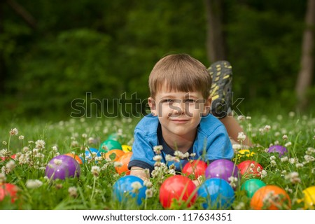 A five year old boy lays in the grass surrounded by colorful toy balls. The boy has expressions of fun and happiness. - stock photo