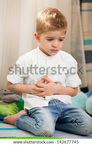 A five year old child having an abdominal pain. A five year old child having a pain in the belly, holding hands over - stock photo