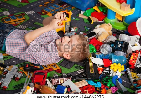 A five year old child playing in his room with a lot of toys around him - stock photo